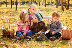 Four happy children playing in park with fruits Royalty Free Stock Photo