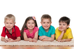 Four happy children on the white carpet Stock Image