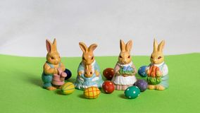Four easter bunnies. child`s with eggs on green meadow. Four happy easter bunnies with colored easter eggs on green meadow Royalty Free Stock Image