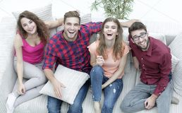 Four happy friends laughing while sitting on the couch. In the living room Royalty Free Stock Images