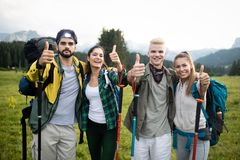 Four happy friends are looking on mountains and having fun together royalty free stock image
