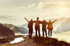 Happy friends travel expedition concept. Four happy friends are looking on mountains and having fun together. Space for text. Travel concept stock photos