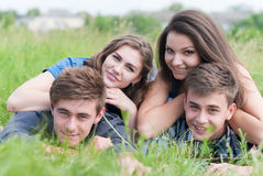 Four happy friends lying together on green grass outdoors Royalty Free Stock Images