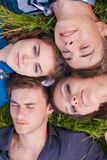 Four happy friends lying together on green grass outdoors Royalty Free Stock Image