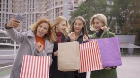 Four happy friends with shopping bags and taking selfie. Four fashion women in the city. Leisure together. Girls. Enjoying their purchases. Shopaholism stock footage