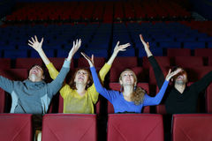 Four happy friends sit in cinema theater Royalty Free Stock Image