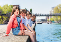 Four happy friends sitting in a line on embankment Stock Images