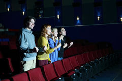 Four happy friends stand, look at screen in cinema theater. Royalty Free Stock Photography