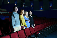 Four happy friends stand and look at screen in cinema theater. royalty free stock photo