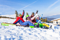 Four happy friends wearing goggles with hands high. Four happy smiling friends wearing goggles with skis sitting together lifting hands up in the air on the royalty free stock photos