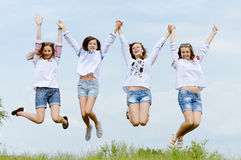 Four happy girl friends jumping high in blue sky Stock Photography