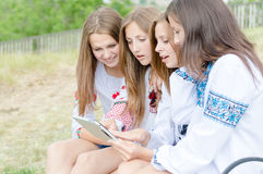Four happy girl friends and tablet computer Stock Image