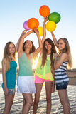 Four happy girls on the beach. Four young happy women on the beach raising the arms up towards the sky, holding colourful balloons, in front of summer sunset Royalty Free Stock Image