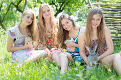 Four happy girls holding rabbits Royalty Free Stock Images