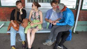 Four happy hipster young friends waiting a train on the railway station. They are siting, talking, exchanging opinions stock footage