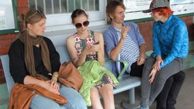 Four happy hipster young people waiting a train on the railway station. They are siting, talking, exchanging opinions. Joking and fooling around. Day stock footage