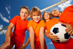 Four happy kids with football portrait. Four happy kids in orange T-shirt portrait from below with football royalty free stock photos
