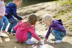 Four happy kids playing by a river. Three little sisters and their brother playing by a river on beautiful sunny autumn day Stock Photo