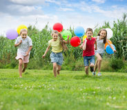 Four happy kids running on green lawn Stock Photo