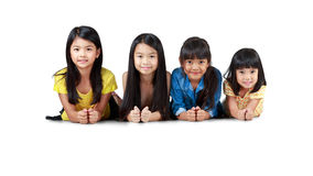 Four happy little asian girls laying on the floor. Isolated over white royalty free stock photos