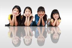 Four happy little asian girls laying. On the floor, Isolated over white with shadows royalty free stock photos