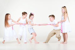 Four happy little girls and boy draw over rope. Four happy little girls and one boy in white clothes draw over pink rope Stock Photo