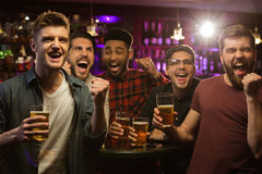 Four happy men holding beer mugs and gesturing. While watching TV in bar or pub Royalty Free Stock Photo