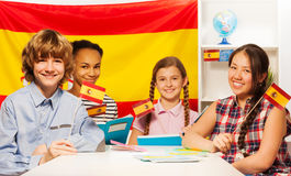 Four happy multiethnic students holding flags Royalty Free Stock Photos