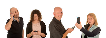 Four happy people with mobile phones, isolated. Four people holding mobile phones on isolated background Royalty Free Stock Photos