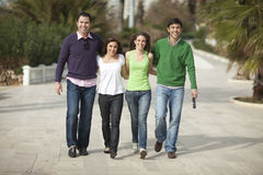 Four happy people walking Royalty Free Stock Photos