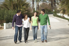Four happy people walking Royalty Free Stock Photo