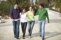 Four happy people walking Royalty Free Stock Images