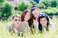 Four happy smiling teen friends in green grass outdoors Royalty Free Stock Image