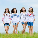 Four happy smiling teen girl friends posing in handmade blouses against blue sky Royalty Free Stock Photography
