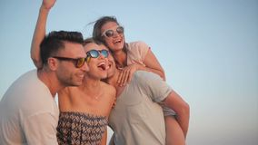 Four Happy Smiling Women and Men Enjoying the Sunset Together on the Seaside During Their Vacation in Summer Time. stock footage