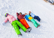 Four happy snowboarders lying in a row Stock Photos