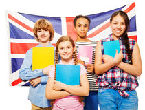 Four happy students standing against British flag Stock Photography