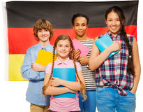 Four happy students standing against German flag Royalty Free Stock Images