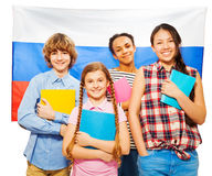 Four happy students standing against Russian flag Stock Image