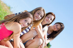 Four happy teen girls against blue sky Royalty Free Stock Photos