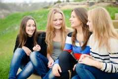 Four happy teen girls friends having fun outdoors. Four happy young women friends having fun outdoors on the green grass background Stock Photo