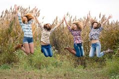 Four happy teenage friends outdoors jumping Stock Image