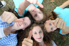 Four happy teenage girls giving thumbs ups Stock Image