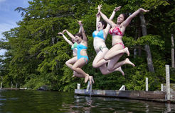 Four happy teenage girls jumping into lake. Four happy teenage girls jumping off a dock into Little Squam Lake, New Hampshire.  All are smiling and wear colorful Royalty Free Stock Images