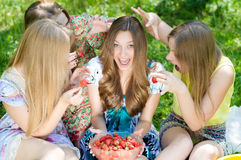 Four happy teenagers and strawberry stock images