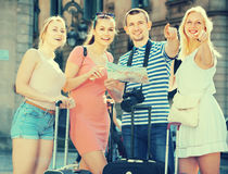 Four happy traveling people using paper map Royalty Free Stock Images