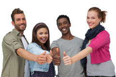 Four happy young friends gesturing thumbs up Royalty Free Stock Image