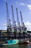 Four harbour cranes. An image of the water front in Bristol england showing four unused old harbour unloading cranes, with boats and water in the foreground stock image