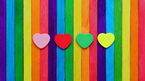 Four hearts in multiple colors on colorful ice-cream sticks line up as rainbow flag. LGBT love concept stock image