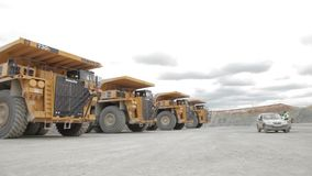 Four heavy dump trucks and service car. In open pit stock video footage